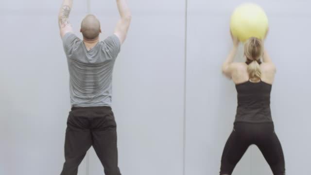 vídeos de stock, filmes e b-roll de cruz de formação classe jogando bolas de medicina no ar - competição