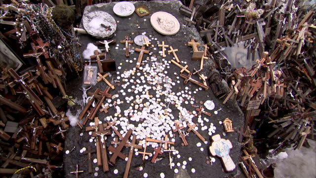 Crosses and crucifixes lie among silver coins at the Hill of Crosses. Available in HD.