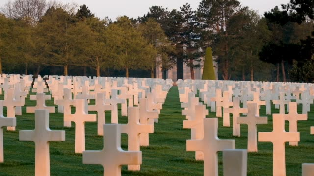 crosses stand over graves at sunrise at normandy american cemetery on april 30, 2019 at colleville-sur-mer, france. the cemetery contains the remains... - normandy stock videos & royalty-free footage