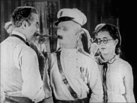 stockvideo's en b-roll-footage met b/w 1927 cross-eyed man in uniform (ben turpin) grabbing long cigar with mouth / feature - 1927