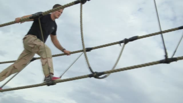 vídeos de stock, filmes e b-roll de crossfit trainers navigate a ropes course designed by navy seals on the beach in san diego california as part of an orientation seminar male trainers... - campo de treinamento militar