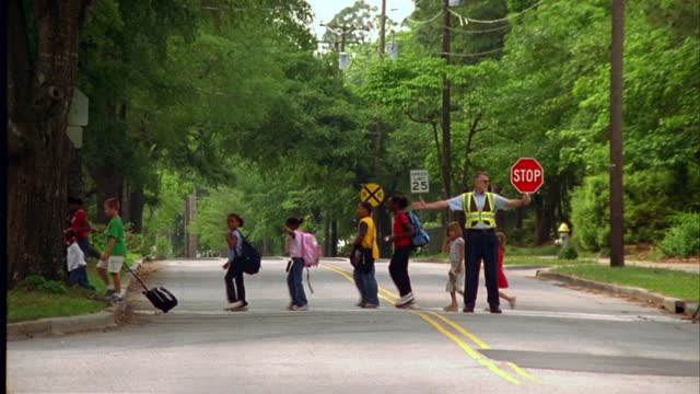 vídeos de stock e filmes b-roll de a crossing guard holds stop sign as children cross a street on their way to school. - stop