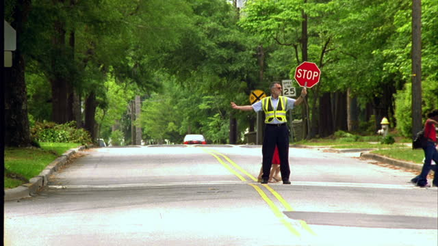 A crossing guard holds stop sign as children cross a street on their way to school.