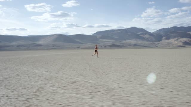 vídeos y material grabado en eventos de stock de cruzando frente a una mujer en el desierto - surrealista