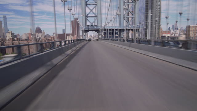 crossing over the manhattan bridge revealing the bridges arches and city backdrop. - car point of view stock videos and b-roll footage