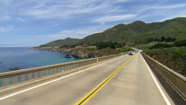 stockvideo's en b-roll-footage met pov crossing rocky creek bridge on u.s. 1 overlooking california coastline, gorda, california, usa - tweebaansweg