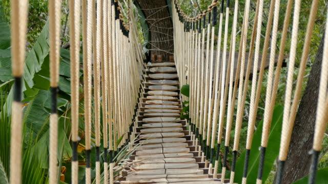crossing the rope bridge - hanging stock videos & royalty-free footage