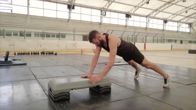 vídeos de stock e filmes b-roll de crossover push ups on aerobic stepper, panning shot - one mid adult man only