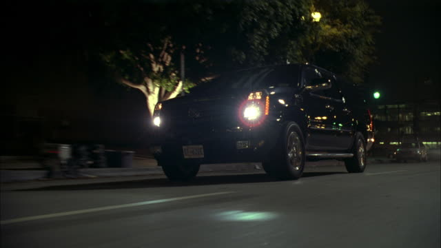 stockvideo's en b-roll-footage met ts crossover suv driving on city street at night and making a u-turn through traffic - sports utility vehicle