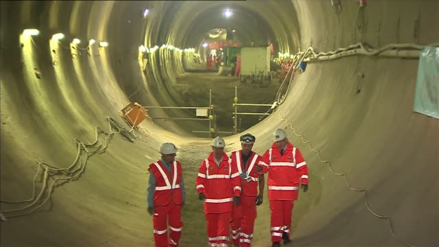 tunnelling completed in london crossrail workers in helmets with boring machine 'victoria' and banner reading 'the big east west breakthrough' in... - クロスレール路線点の映像素材/bロール