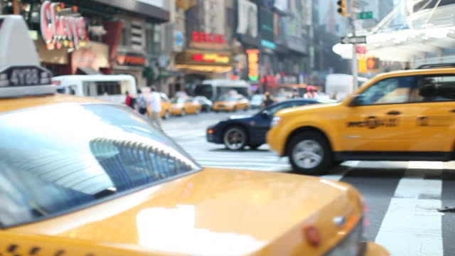 crossroad with yellow cabs driving past - yellow taxi stock-videos und b-roll-filmmaterial