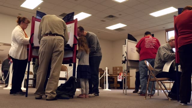 a crosssection of white michigan voters stand at voting stations and mark their ballots in the 2016 presidential election michigan voters gave donald... - booth stock videos & royalty-free footage