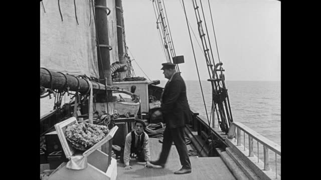 vídeos de stock, filmes e b-roll de 1923 crouched on deck, cabin boy (buster keaton) tries to avoid being stood on by ship captain (joe roberts) - 1923