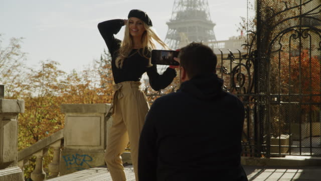 vídeos de stock, filmes e b-roll de crouching man with cell phone photographing woman posing near eiffel tower / paris, ile de france, france - boina