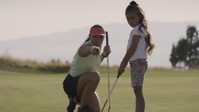 crouching woman golfer teaching putting to girl / cedar hills, utah, united states - golf swing stock videos & royalty-free footage