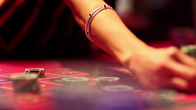 CU R/F Croupier dealing large stack of casino chips at roulette table / Las Vegas, Nevada, USA