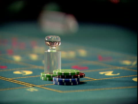 croupier's hand tidies pile of gambling chips on green baize table - casino stock videos & royalty-free footage