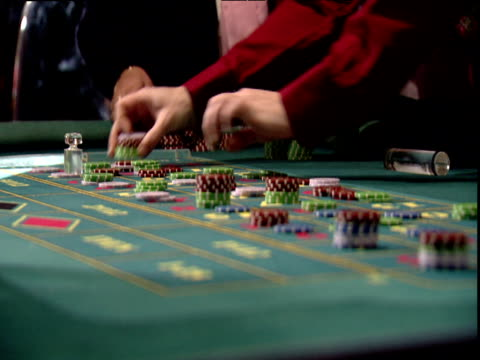 croupier's hands with red cuffs sweep gambling chips from table - casino stock videos & royalty-free footage