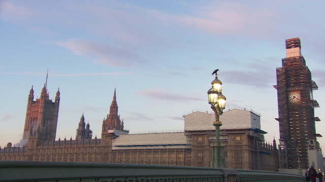 A crow crowing on top of a lamp post outside the Houses of Parliament