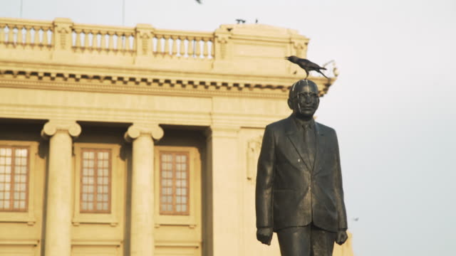 crow on statue head with excrements at old colonial parliament of colombo, sri lanka - colonial stock-videos und b-roll-filmmaterial