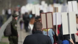 Crowd activists at a rally with posters are on the road walking banner Europe 4K