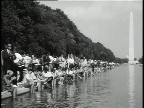 vídeos de stock e filmes b-roll de crowd applauding / crowd sitting at edge of reflecting pool / marian anderson on stage / crowd watching from trees - 1963