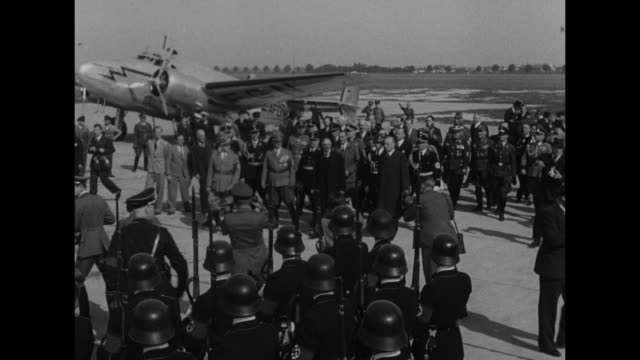 vídeos y material grabado en eventos de stock de crowd approaches plane on runway in munich, nazi soldiers in foreground stand at attention with bayonets / flagpoles with bottom edges of flags... - en el borde