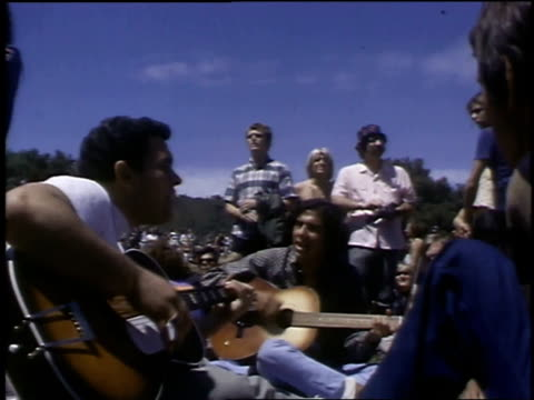 crowd at a lovein with man making a speech on a microphone hippies playing guitars and singing and other standing around listening and singing - hippie stock videos & royalty-free footage