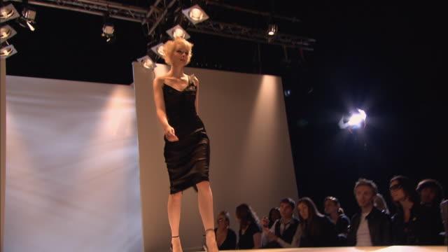 MS PAN Crowd at fashion show as woman walks past on catwalk/ TU LA MS woman walking on catwalk, turning, and walking away/ London, England