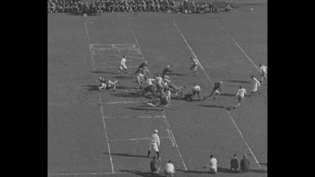 crowd at forbes field during college football game between university of pittsburgh and carnegie tech / carnegie tech kicks off to pitt on sunny... - インターセプト点の映像素材/bロール