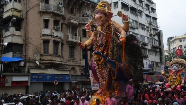 crowd at religious procession during ganpati visarjan ceremony, mumbai, maharashtra, india - フロート車点の映像素材/bロール