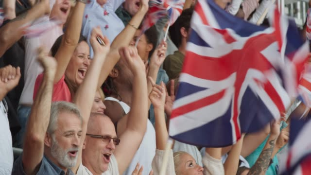 crowd at the stadium cheering loudly while waving british flags - british culture stock videos & royalty-free footage