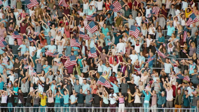 ld crowd at the stadium standing up and happily waving american flags to the music - stars and stripes stock videos & royalty-free footage