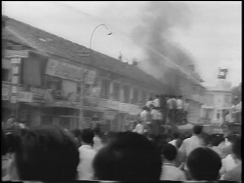 b/w 1963 crowd by building being hosed down / smoke rising / south vietnam / newsreel - south vietnam stock videos & royalty-free footage