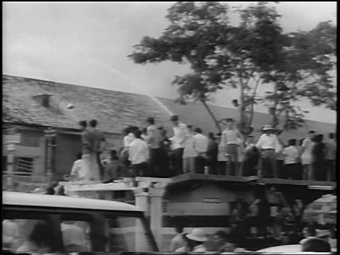 B/W 1963 crowd by building being hosed down / South Vietnam / newsreel