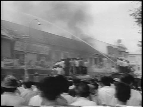 PAN crowd by building being hosed down / South Vietnam / newsreel