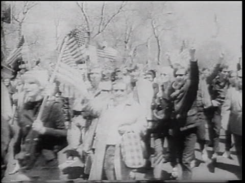 B/W 1967 crowd carrying American flags making peace/victory signs walking in parade / NYC