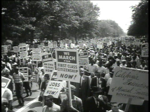 vídeos de stock e filmes b-roll de crowd carrying signs marches / man smokes cigar and watches march - 1963
