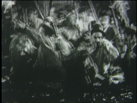 B/W 1925 crowd carrying torches in water points + starts to run