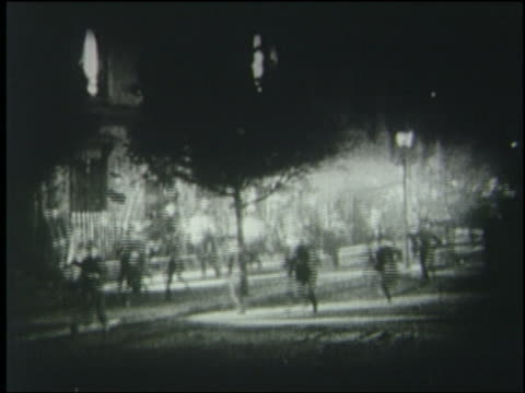 B/W 1925 crowd carrying torches runs on Paris street at night