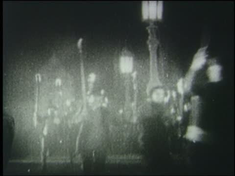 b/w 1925 crowd carrying torches runs past camera on paris street at night - 1925 stock videos & royalty-free footage