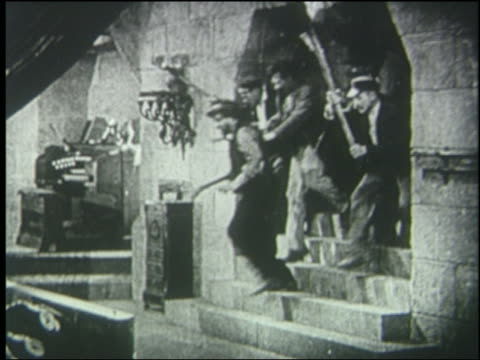 b/w 1925 crowd carrying torches runs thru doorway + down stairs - 1925 stock videos & royalty-free footage