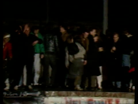 Crowd celebrating on top of wall Opening of Berlin Wall