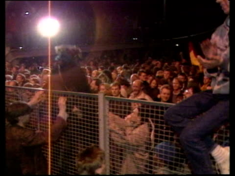 crowd cheer as people climb over fence at checkpoint charlie opening of berlin wall 09 nov 89 - bbc archive stock-videos und b-roll-filmmaterial