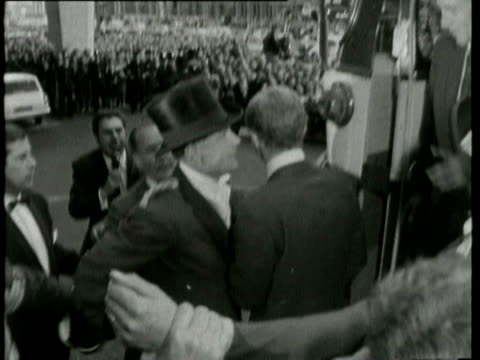 crowd cheering and waving England football team members including Bobby Charlton passing World Cup trophy from one to another prime minister Harold...