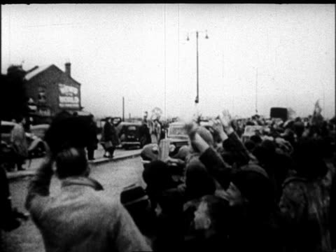 b/w 1938 crowd cheering as motorcade passes on street / after signing of munich pact / london - 1938年点の映像素材/bロール