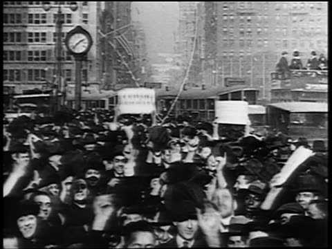 B/W 1919 crowd cheering holding newspaper throwing confetti in NYC street at end of WWI