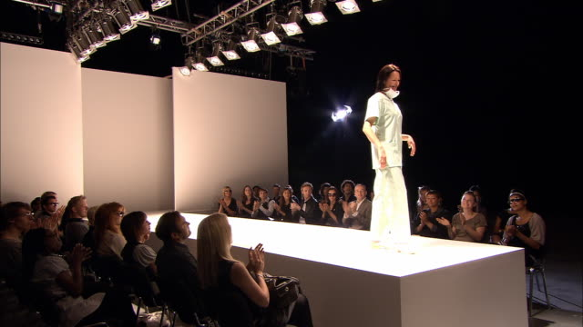 MS Crowd clapping at fashion show/ TU PAN Woman walking on catwalk in hospital scrubs/ TD People clapping/ London, England