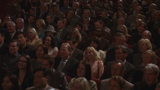 A crowd clapping in an auditorium.