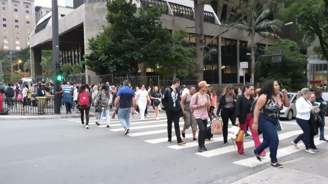 vídeos de stock, filmes e b-roll de multidão que cruza um cruzamento de pedestre na avenida de paulista. - street